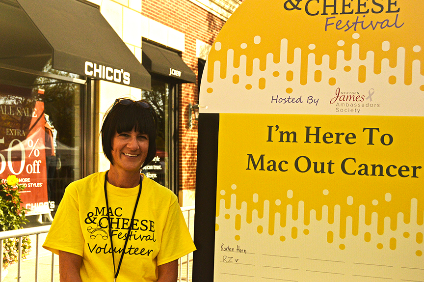 2019 Columbus Mac and Cheese Festival woman with dark hair volunteer in front of event sign