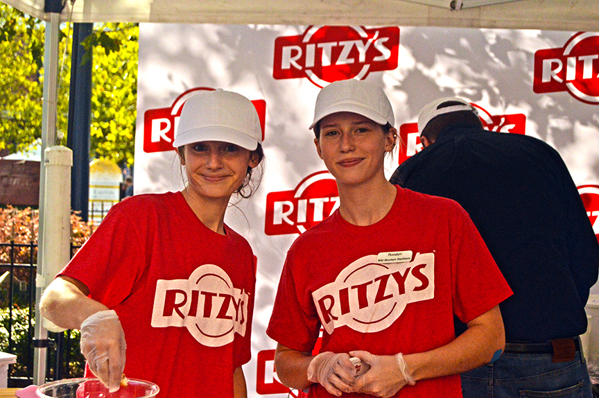 Two women in red shirts and white caps from Ritzy's at the Mac and Cheese Festival