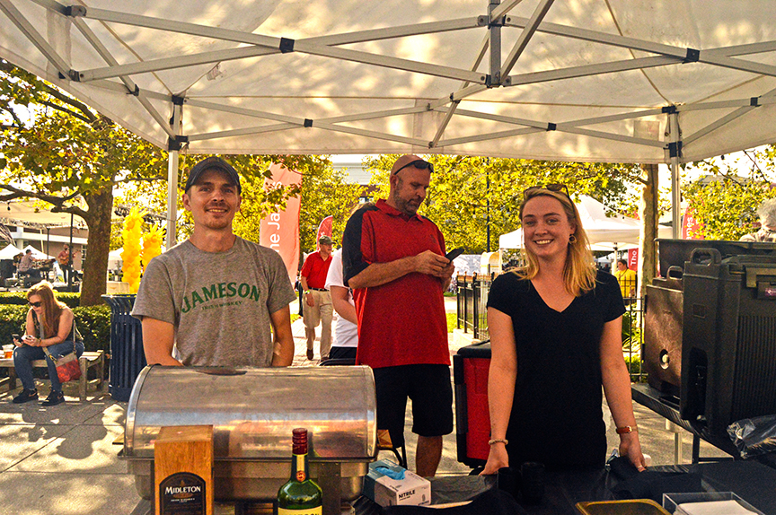 Man with cap and grey shirt next to blond woman in black dress at Mac and Cheese Festival