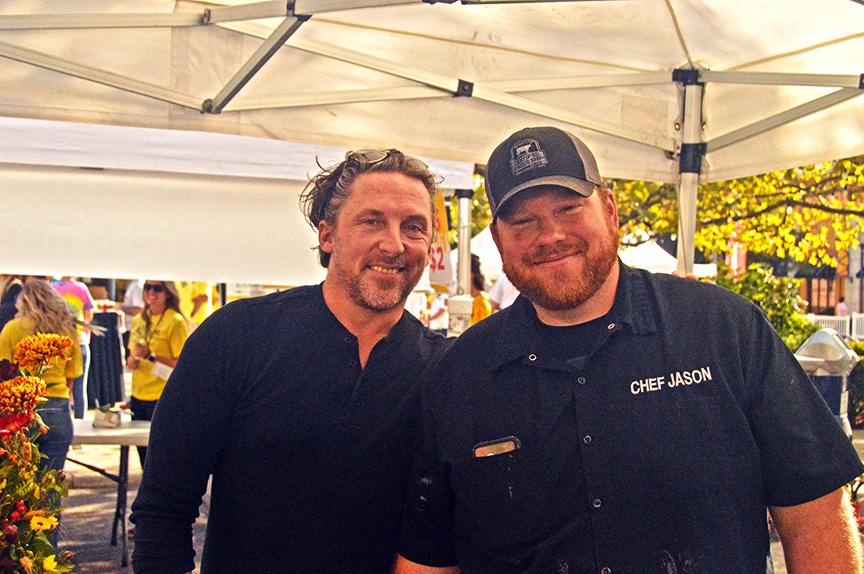 Two male chefs in black shirts, one with cap under white tent roofing at event