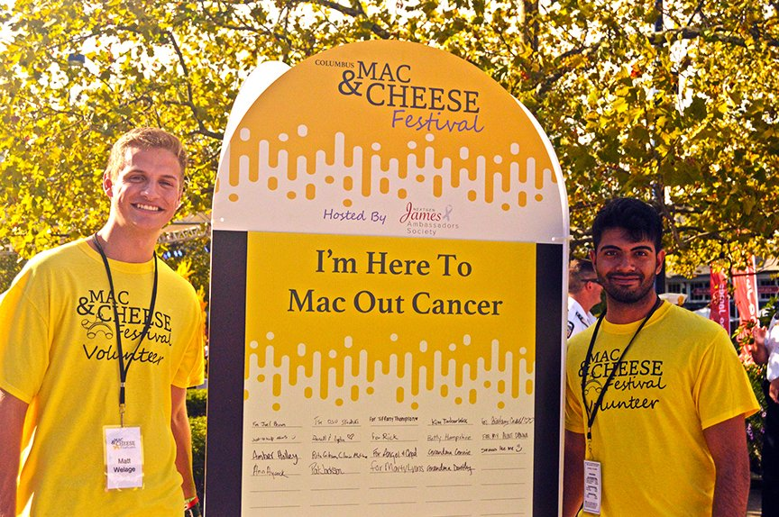 Two male NextGen Ambassadors posing with Mac Out Cancer sign in-between