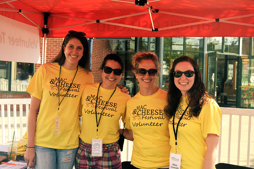 Four women under red tent roof wearing yellow mac and cheese fest t-shirts