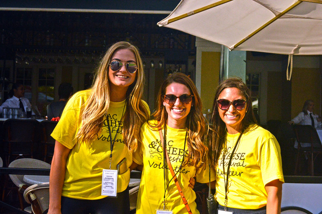 Three women dressed in yellow t-shirts posing in front of Brio at Mac and Cheese Fest