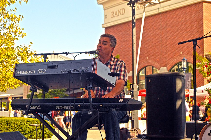 Seated keyboardist sings into mic at event