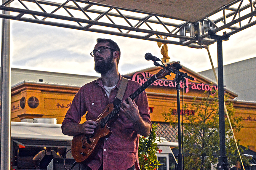 Guitarist stroking chords at Mac and Cheese Fest