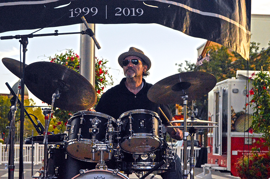 seated drummer with hat playing at festival