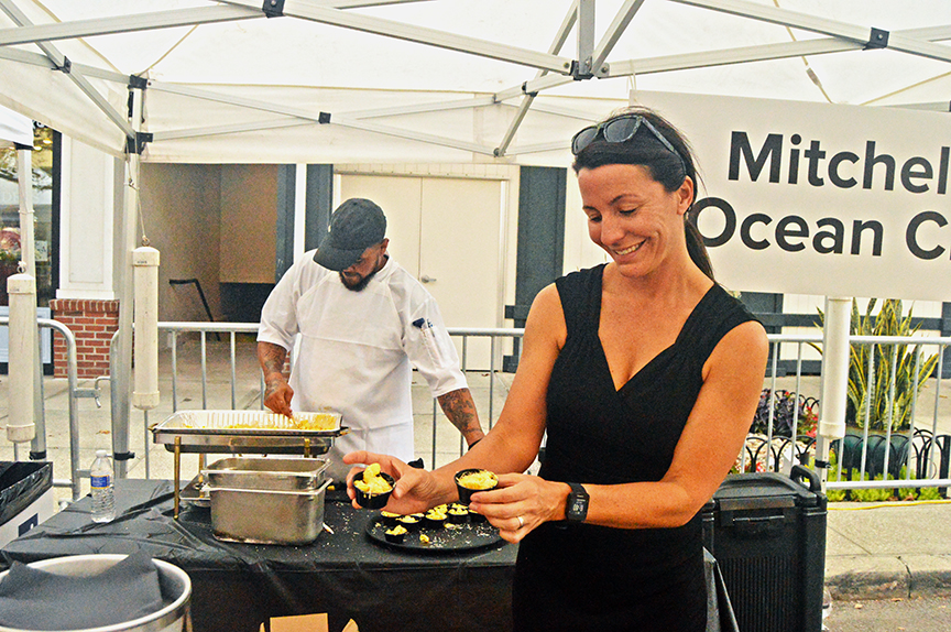 Woman in black dress holds mac and cheese samples in both hands