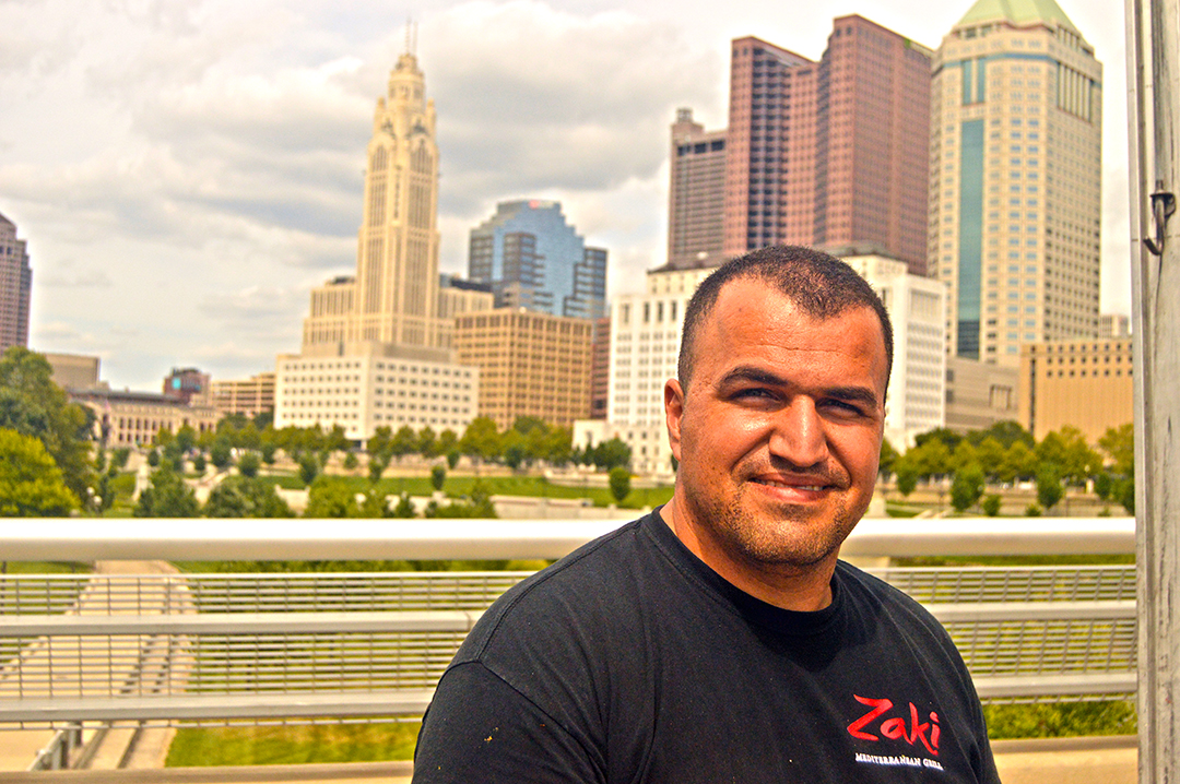 Ahmed Oaraja of Zaki Grill poses in front of buildings, Columbus Food Truck Festival