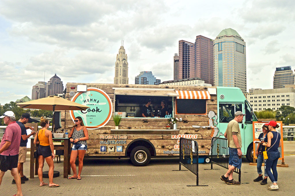 Momma Can Cook vehicle surrounded by patrons in front of skyline, Columbus Food Truck Festival