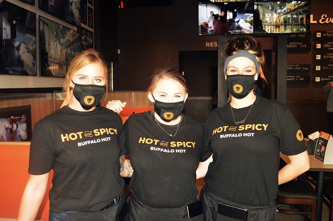 Three Buffalo Wings & Rings waitresses posing in black shirts.