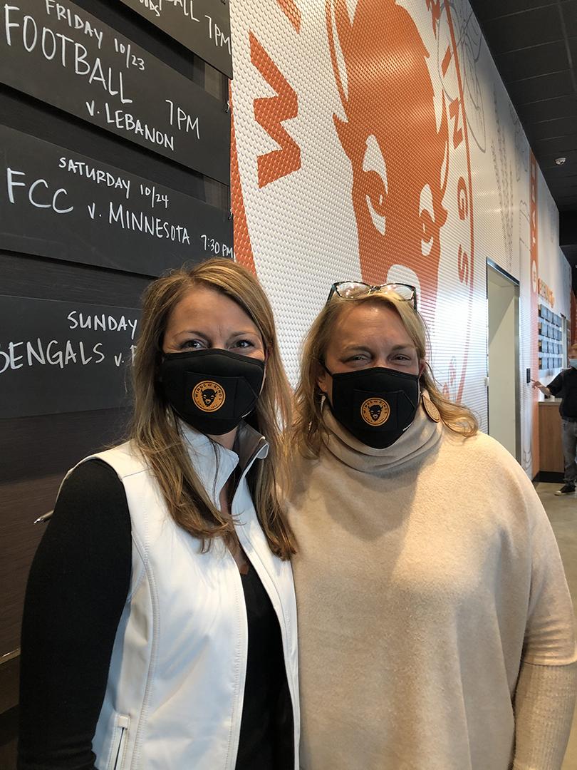 Vicki & Danielle pose next to BW&W wall logo.